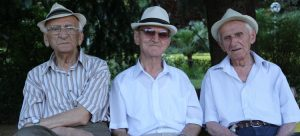 3 happy old men sitting on a bench because they got a reverse mortgage in Sheridan